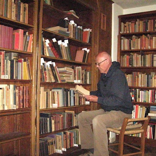 Dr. Müller vor der Bücherwand in der Bibliothek